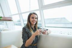 A mulher de sorriso com uma xícara de café em suas mãos senta-se em um café claro moderno Imagens de Stock