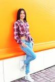 Mulher de sorriso consideravelmente nova que veste uma camisa quadriculado e calças de brim Foto de Stock