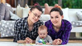 Mulher de sorriso consideravelmente ocasional de dois pares e pouca criança bonito que levantam olhando a câmera video estoque