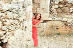 Mulher de sorriso contra uma parede de pedra Foto de Stock