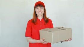 Mulher de sorriso da entrega no uniforme vermelho Fêmea no tampão, no t-shirt, nas calças de brim que trabalham como o correio ou filme