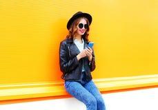 A mulher de sorriso da forma está usando o smartphone no revestimento preto da rocha Imagem de Stock Royalty Free