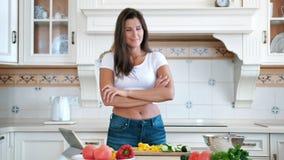 Mulher de sorriso da possibilidade remota média que cozinha estar na cozinha com mãos cruzadas filme