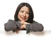 Mulher de sorriso da raça misturada que inclina-se no sinal branco vazio Imagem de Stock Royalty Free