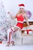 Mulher de sorriso de Santa perto da árvore de Natal Fotos de Stock Royalty Free