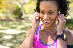 Mulher de sorriso do basculador que ajusta seus fones de ouvido no parque Imagem de Stock Royalty Free
