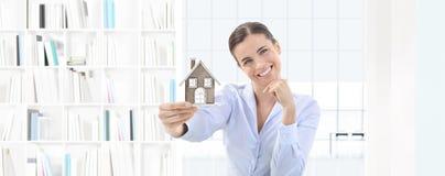 Mulher de sorriso do conceito home que mostra o modelo da casa, bens imobiliários e foto de stock royalty free