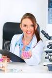 Mulher de sorriso do doutor que dá medicamentos de venta com receita Fotografia de Stock