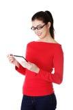 Mulher de sorriso do estudante no eyewear usando uma tabuleta Fotografia de Stock Royalty Free