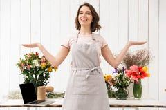 Mulher de sorriso do florista que está a tabela próxima com flores diferentes imagem de stock