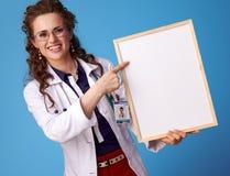 Mulher de sorriso do médico que aponta na placa vazia no azul Foto de Stock Royalty Free