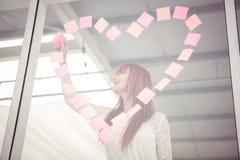 Mulher de sorriso do moderno que faz um coração no post-it Imagens de Stock