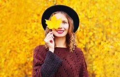 A mulher de sorriso do retrato do outono esconde suas folhas do amarelo do bordo do olho imagens de stock