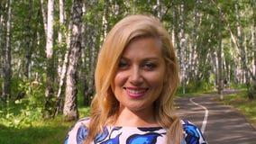 Mulher de sorriso do retrato que olha e que levanta na câmera no fim do parque do verão acima filme