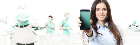 Mulher de sorriso dos cuidados dentários que mostra o telefone esperto na clínica do dentista imagens de stock