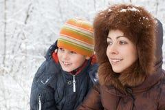 Mulher de sorriso e menino alegre no inverno na madeira Fotos de Stock Royalty Free