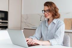 Mulher de sorriso elegante nos vidros e em camisa listrada usando o portátil Imagens de Stock Royalty Free