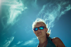 Mulher de sorriso em óculos de sol do esporte sobre o céu azul Imagens de Stock Royalty Free