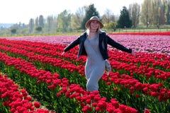 Mulher de sorriso em campos da tulipa Fotografia de Stock Royalty Free