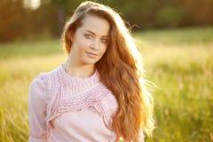 Mulher de sorriso em um campo no por do sol foto de stock royalty free