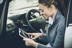 Mulher de sorriso em um carro com tabuleta imagem de stock royalty free