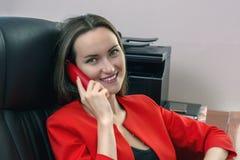 A mulher de sorriso em um terno de negócio vermelho senta-se em uma cadeira de couro e na fala no telefone Imagens de Stock Royalty Free