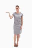 Mulher de sorriso em um vestido que apresenta algo Imagens de Stock