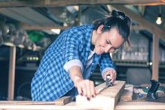 Mulher de sorriso em uma fita métrica de medição da oficina home uma placa de madeira antes de ver, carpintaria imagens de stock royalty free