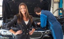 Mulher de sorriso em uma garagem de conservação do carro imagem de stock