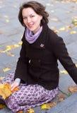 Mulher de sorriso encantadora com folhas de outono   Imagens de Stock