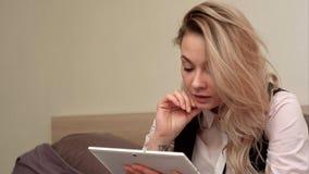 A mulher de sorriso entusiasmado que tem o vídeo chama a tabuleta ao sentar-se em sua cama Fotos de Stock Royalty Free