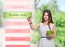 A mulher de sorriso escolhe o alimento saudável na tela futurista Fotos de Stock