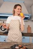 A mulher de sorriso está bebendo o suco de laranja e está provando o bolo que fez em sua cozinha foto de stock royalty free