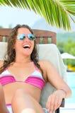 A mulher de sorriso está sentando-se na cadeira no poolside imagens de stock royalty free
