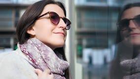 Mulher de sorriso europeia do comprador do close-up que aprecia a compra que olha na mostra de vidro da loja video estoque