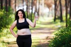 Mulher de sorriso excesso de peso nova com uma garrafa do outd claro da água fotos de stock royalty free