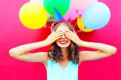 A mulher de sorriso feliz é couros crus seus olhos com as mãos que têm o divertimento sobre um rosa colorido dos balões do ar foto de stock royalty free