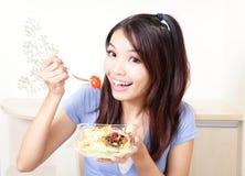 Mulher de sorriso feliz com salada em casa Fotos de Stock Royalty Free
