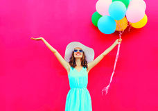 A mulher de sorriso feliz da forma com os balões coloridos de um ar está tendo o divertimento no verão sobre um fundo cor-de-rosa