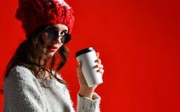 A mulher de sorriso feliz da forma guarda o copo de café no fundo vermelho da parede fotografia de stock
