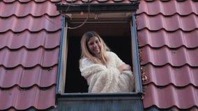A mulher de sorriso feliz do retrato abre uma janela dos olhares da casa na rua video estoque