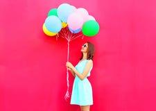A mulher de sorriso feliz está olhando nos balões coloridos de um ar que têm o divertimento sobre o fundo cor-de-rosa Fotos de Stock Royalty Free