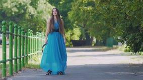Mulher de sorriso feliz nos suportes azuis do vestido que levantam a dança, movimento lento fora filme