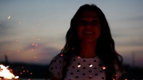 Mulher de sorriso feliz nova, dançando dentro com o chuveirinho no por do sol no movimento lento, com os fogos-de-artifício no po filme