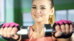 Mulher de sorriso feliz nova no sportswear, fazendo o exercício da aptidão com pesos vídeos de arquivo