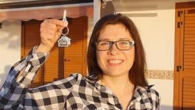 Mulher de sorriso feliz que guarda chaves da casa de sua casa nova