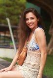 Mulher de sorriso feliz que senta-se no vestido da praia Foto de Stock