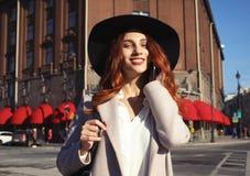 Mulher de sorriso feliz que veste o chapéu à moda, revestimento Passeio modelo na rua da cidade europeia fotos de stock royalty free