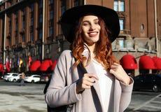 Mulher de sorriso feliz que veste o chapéu à moda, revestimento Passeio modelo na rua da cidade europeia imagem de stock
