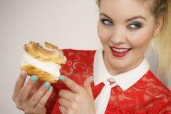 A mulher de sorriso guarda o bolo do sopro de creme foto de stock royalty free